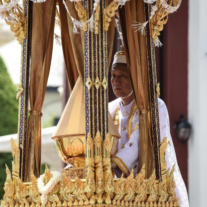 TOPSHOT - One of the royal doctors holds an urn containing the ashes of the late Thai king Bhumibol Adulyadej atop a royal chariot during the funeral procession to transport his ashes from the Royal Crematorium to the Grand Palace, in Bangkok on October 27, 2017. Thailand's new king picked bits of bone and ash from his father's remains on October 27 to be enshrined as royal relics, after the cremation of the late King Bhumibol Adulyadej capped an extravagant funeral that brought the nation to a standstill. / AFP PHOTO / Lillian SUWANRUMPHA